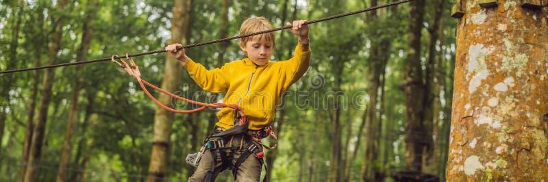 Chłopiec w linowym parku Aktywny fizyczny odtwarzanie dziecko w świeżym powietrzu w parku Trenować dla dzieci zdjęcia royalty free