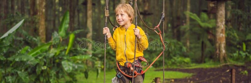 Chłopiec w linowym parku Aktywny fizyczny odtwarzanie dziecko w świeżym powietrzu w parku Trenować dla dzieci zdjęcie stock