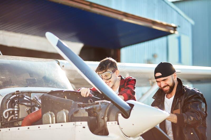 Chłopiec w lotników szkłach śmia się wpólnie przy dowcipami mężczyźnie w pilotowej kurtce i obraz royalty free