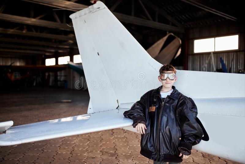 Chłopiec w lotników szkłach i wielkiej skóra pilota kurtce, stojaki zbliża ogon samolot zdjęcia stock