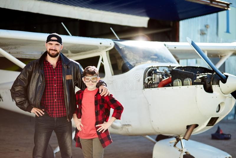 Chłopiec w lotników szkieł odczuciach uradowanych jego ojciec wziąć on hangar dokąd robi remontowym pracom fotografia stock
