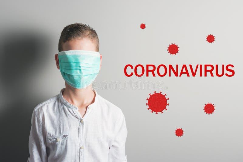 Chłopiec w masce medycznej na twarzy z czerwonym napisem CORONAVIRUS na jasnym tle Epidemia wirusa 2019-nCoV Oddech obrazy royalty free