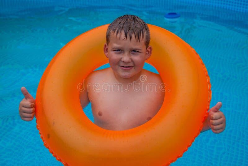 Chłopiec w mieć zabawę w pływackim basenie zdjęcia stock