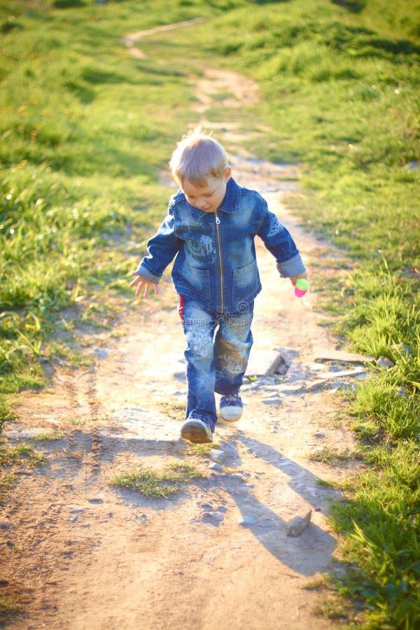 Chłopiec w nakrętce bawić się outdoors w lecie na Pogodnym ciepłym dniu, trawa, zielenie, natura zdjęcia stock