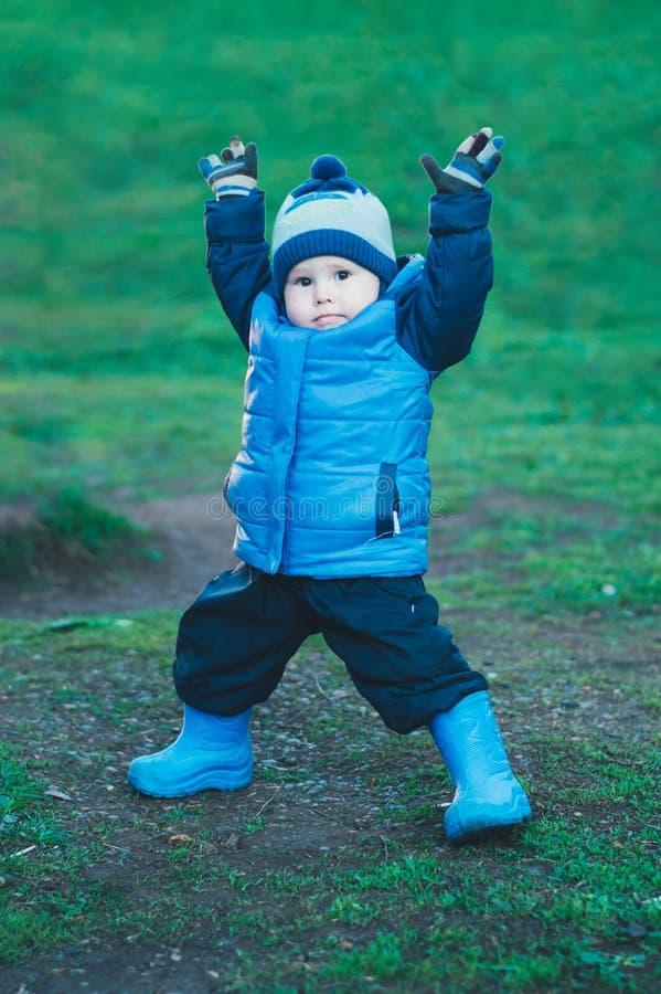 Chłopiec w niebieskiej marynarce robi ćwiczeniom w chmurnej pogodzie zdjęcia royalty free