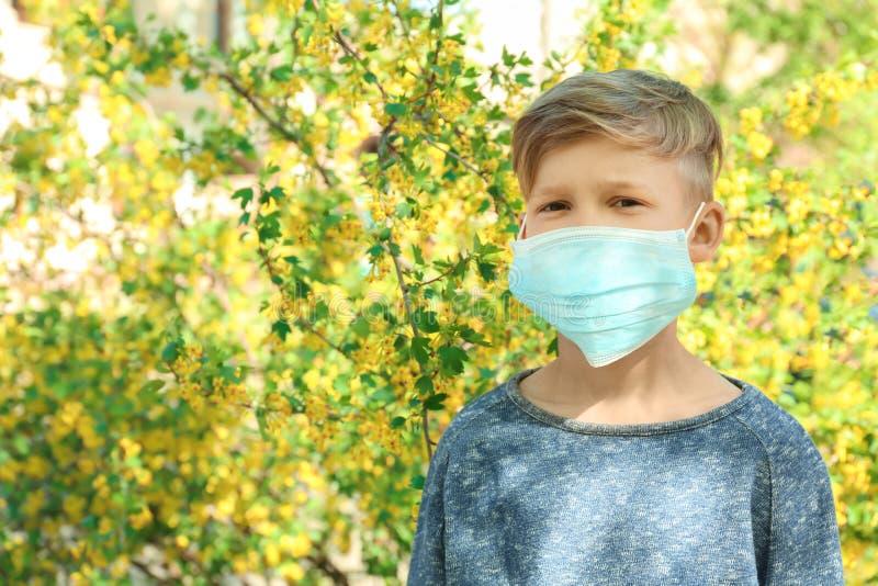 Chłopiec w ochronnej masce blisko kwitnącego drzewa Alergii poj?cie zdjęcia stock
