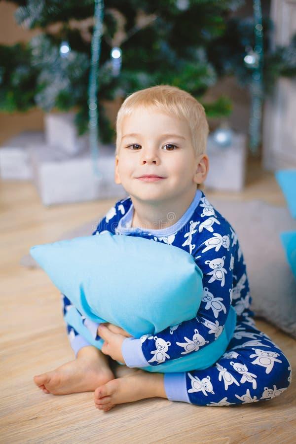 Chłopiec w piżamach z niedźwiedziami uśmiecha się, siedzi i ściska, błękitną poduszkę obrazy royalty free