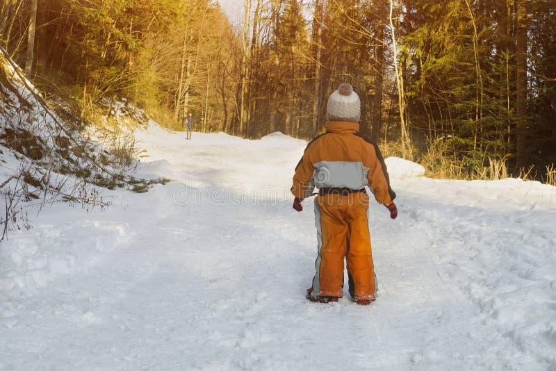 Chłopiec w pomarańczowej kombinezon pozycji na śnieżystej drodze w iglastej las matce jest w odległości Zima słoneczny dzień obraz royalty free