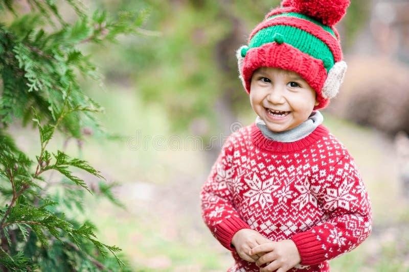 Chłopiec w puloweru i kapeluszu czekaniu dla boże narodzenia w drewnie zdjęcie royalty free