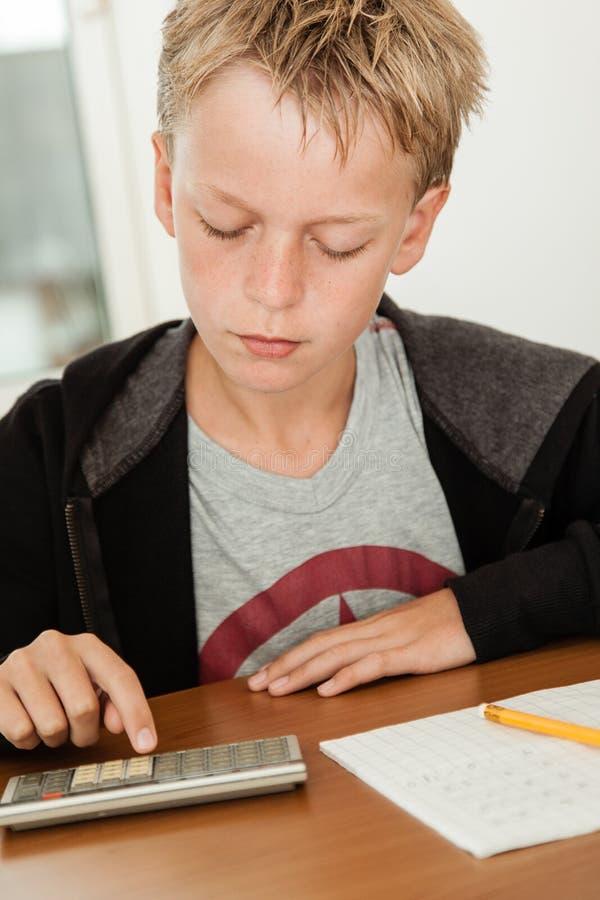 Chłopiec w pulowerze używać kalkulatora sprawdzać jego praca fotografia stock
