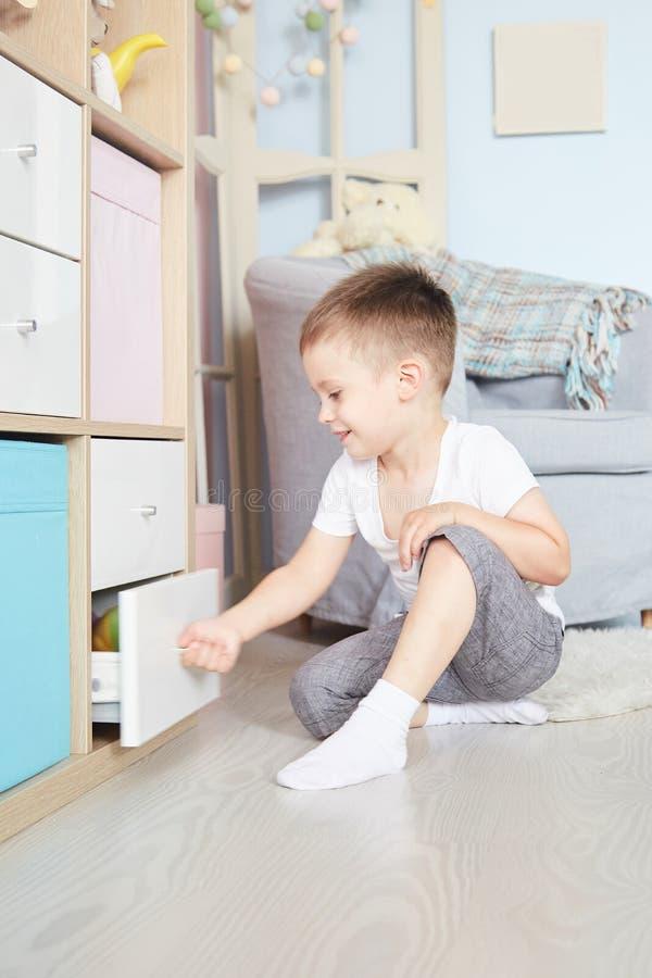 Chłopiec w rękach siedział na podłoga blisko garderoby zdjęcie royalty free