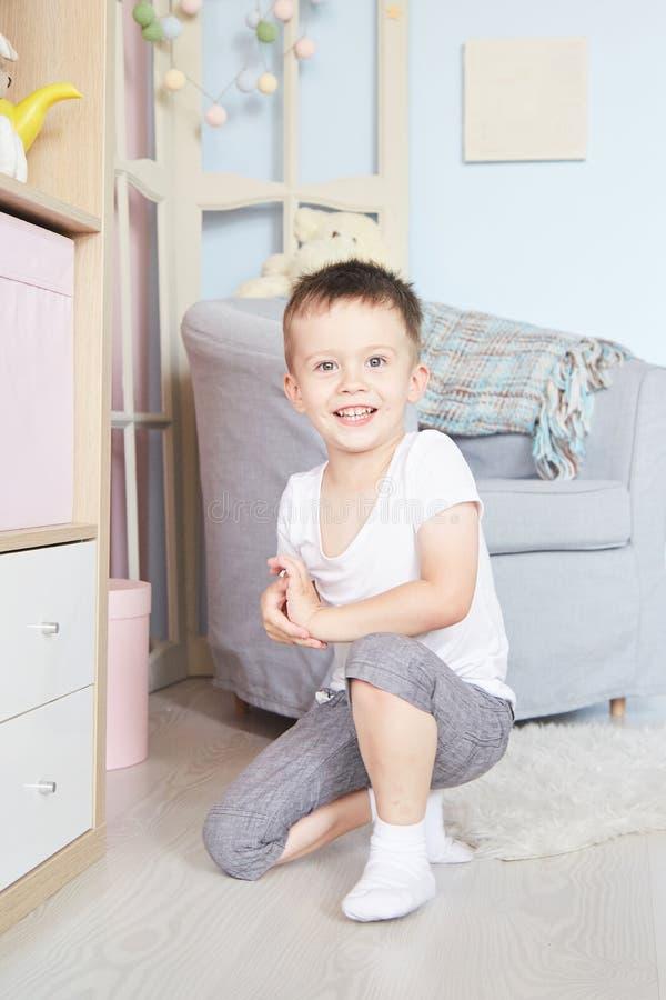 Chłopiec w rękach siedział na podłoga blisko garderoby zdjęcia stock