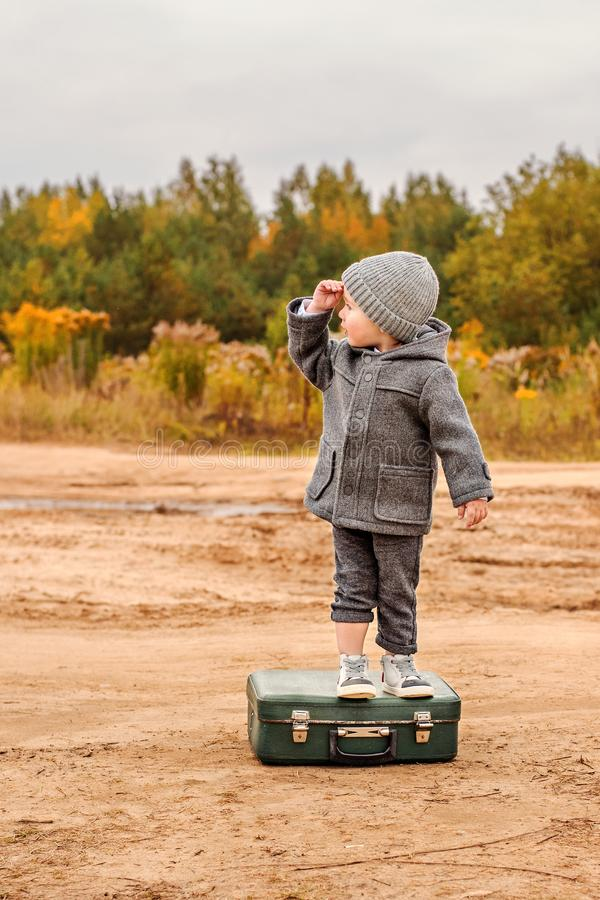 Chłopiec w retro szarość ubraniach wspinał się na starej walizce w poszukiwaniu obraz royalty free