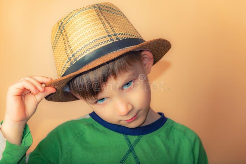 Chłopiec w słomianym kapeluszu przenosi powitanie, portret dziecko na beżowym tle zdjęcia royalty free