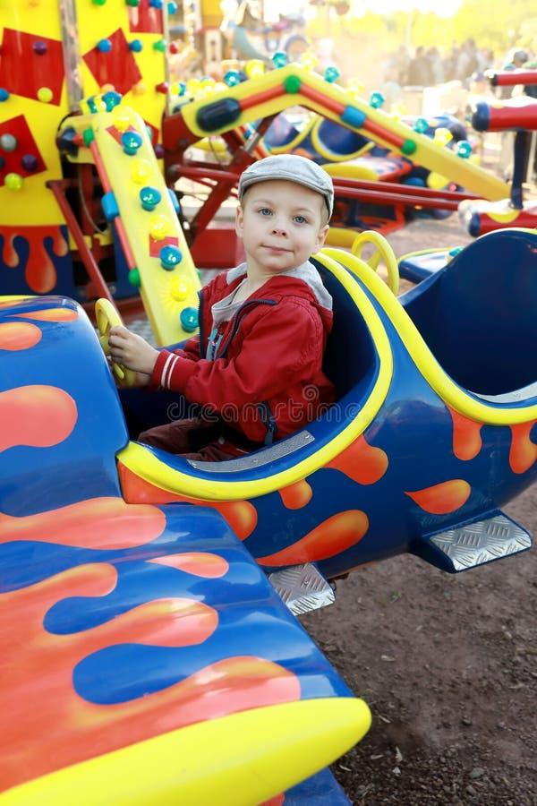 Chłopiec w samolocie na carousel zdjęcie stock