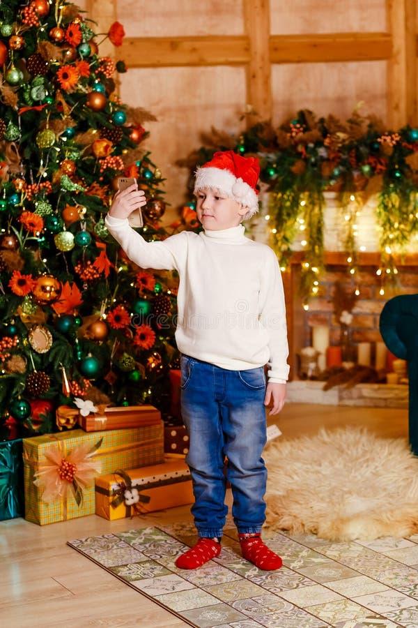 chłopiec w Santa nakrętce z telefonem w jego ręka stojakach blisko wielkiej eleganckiej choinki Dziecko bierze selfie zdjęcia stock