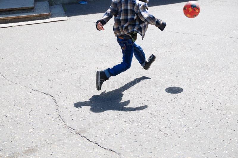 Chłopiec w skoku, dziecko bieg po tym jak piłka bawić się futbol na asfalcie, balowy skok, piłka nożna gracz drużynowy, trenować  fotografia stock