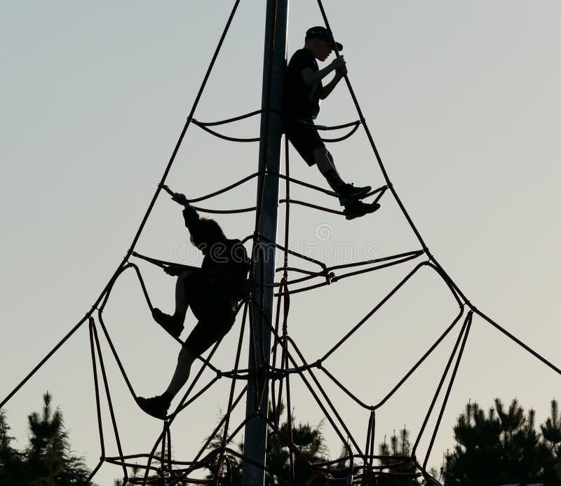 Chłopiec w sylwetce na arkany i słupa przygody wspinaczkowej ramie obraz stock