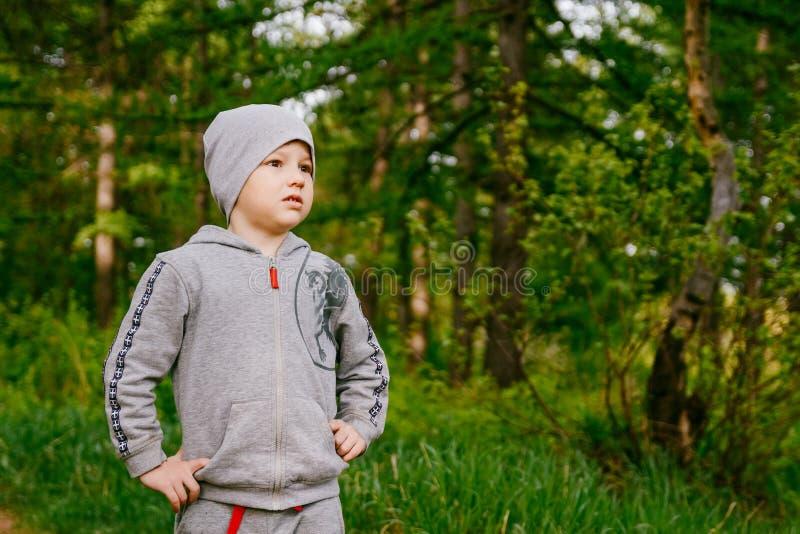 Chłopiec w szarym kapeluszu jest w zielonym lato lesie zdjęcie royalty free