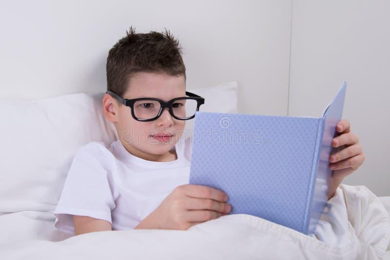 chłopiec w szkłach, kłamający w łóżku i czytaniu książka fotografia royalty free