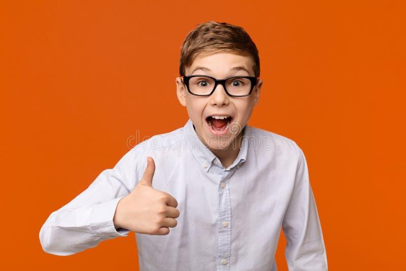 Chłopiec w szkłach pokazuje kciuk w górę gesta fotografia stock