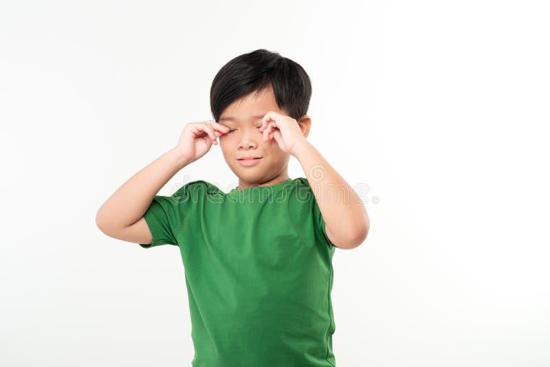 Chłopiec w szkole ocierający się o długą pracę domową zdjęcie stock