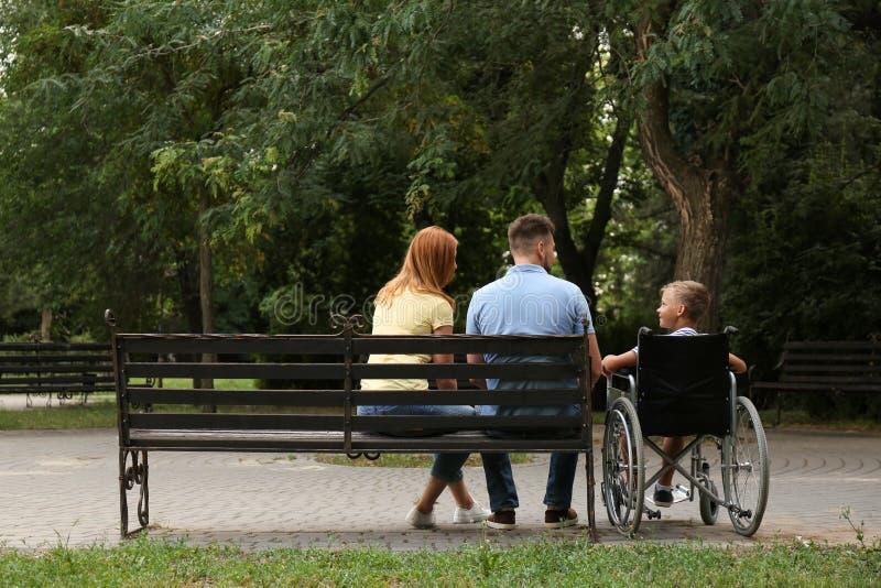 Chłopiec w wózku inwalidzkim z jego rodziną zdjęcia royalty free