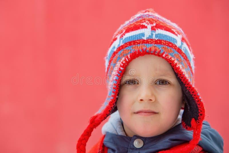 Chłopiec w zima kapeluszu pozach przed czerwonym tłem zdjęcia stock