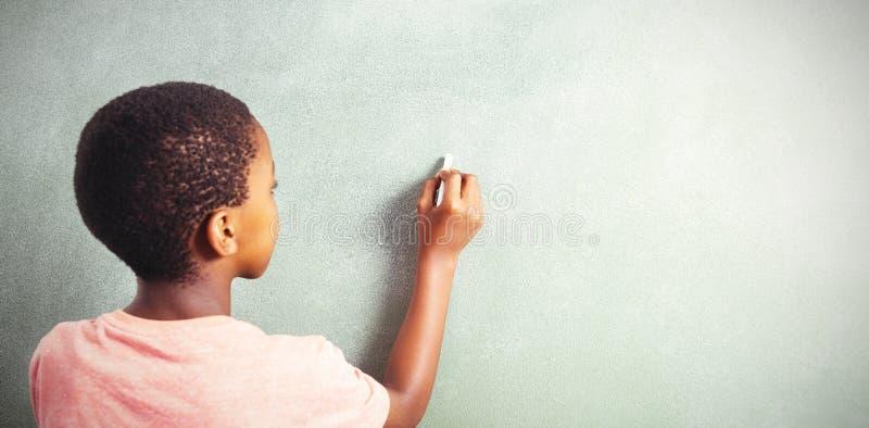 Chłopiec writing z kredą na greenboard w szkole obrazy royalty free