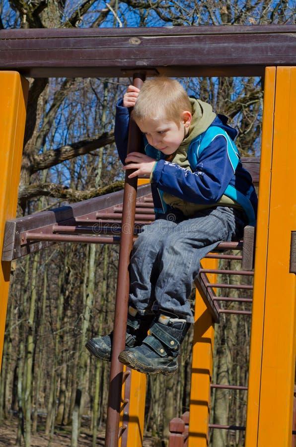 Chłopiec wspina się na boisku obraz royalty free