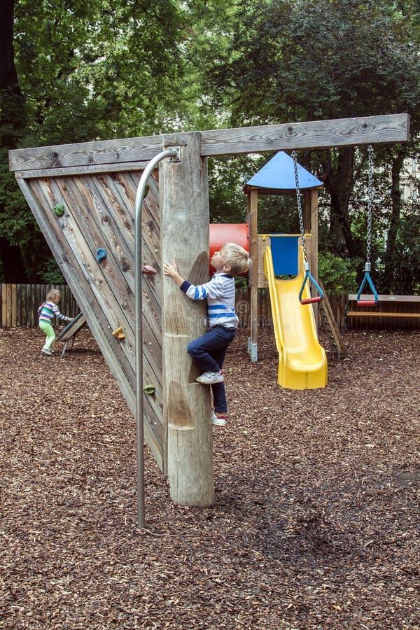chłopiec wspina się na drewniany słup ze stopniami, aby ześlizgnąć się po słupie ognia na nowoczesnym zewnętrznym placu zabaw obraz royalty free