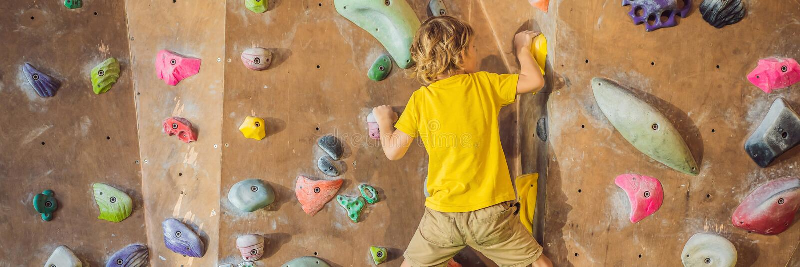 Chłopiec wspina się rockową ścianę w specjalnych butach salowy sztandar, DŁUGI format zdjęcie stock