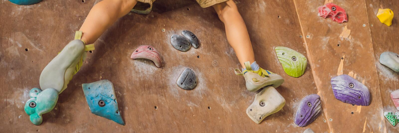 Chłopiec wspina się rockową ścianę w specjalnych butach salowy sztandar, DŁUGI format fotografia royalty free