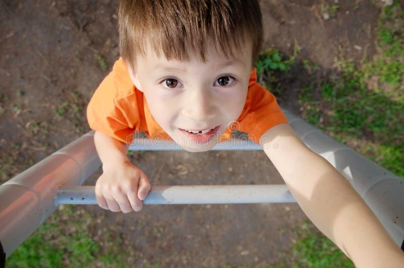 Chłopiec wspinaczkowi schodki i bawić się outdoors na boisku, dziecko aktywność Dziecko portret od above Aktywny zdrowy dziecińst zdjęcia stock