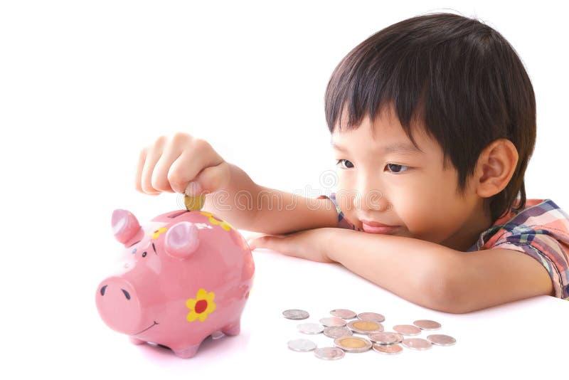 Chłopiec wszywki moneta w prosiątko banka zdjęcie stock
