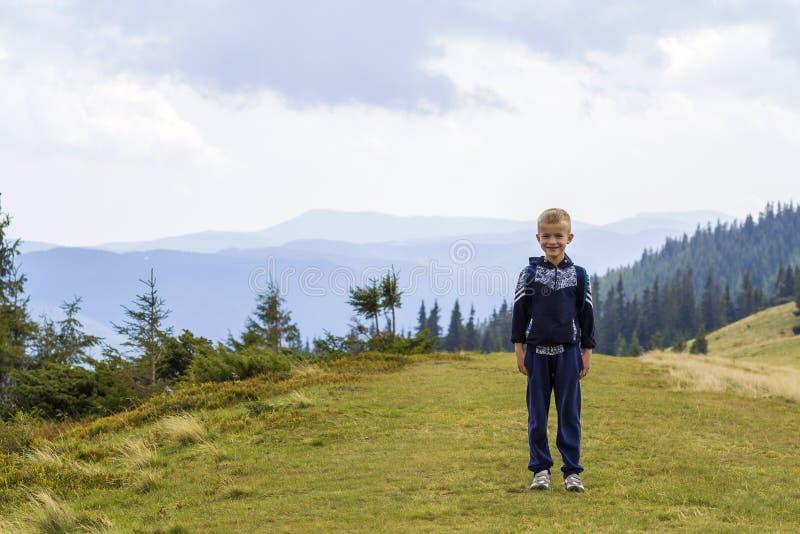 Chłopiec wycieczkuje w scenicznej lato zieleni Karpackich górach z plecakiem Dziecko stoi samotnie cieszyć się krajobrazową górę  obraz stock