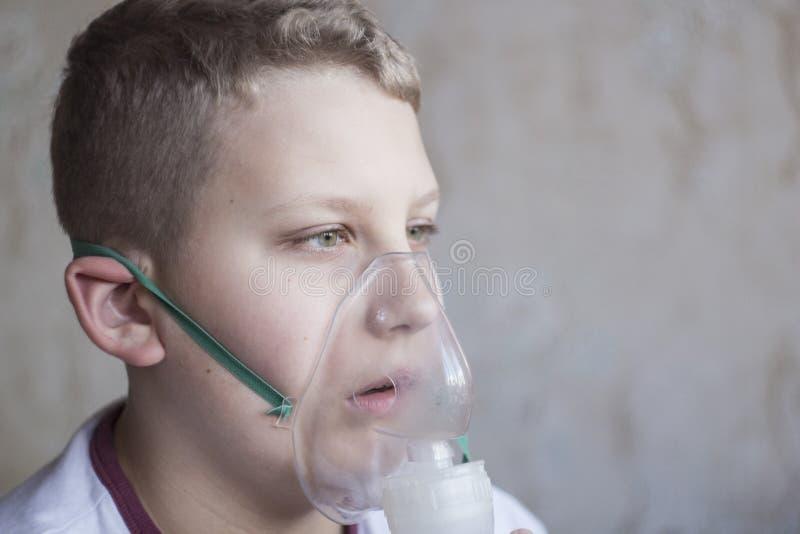 Chłopiec z białego włosy oddychaniem w inhalatorze zdjęcia royalty free