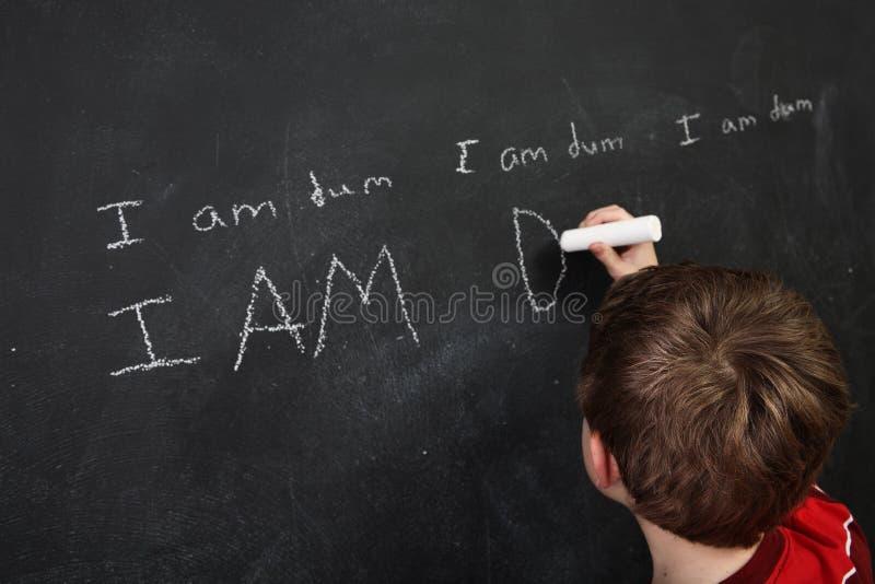 Chłopiec z biednym pisowni i depresji jaźni szacuneku writing na blackboa zdjęcie royalty free