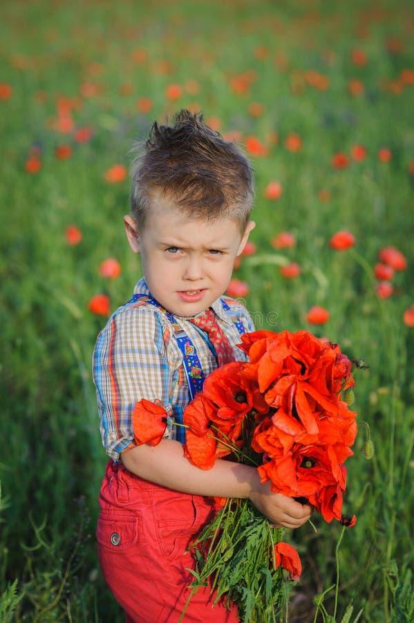 Chłopiec z bukietem czerwoni maczki obrazy royalty free