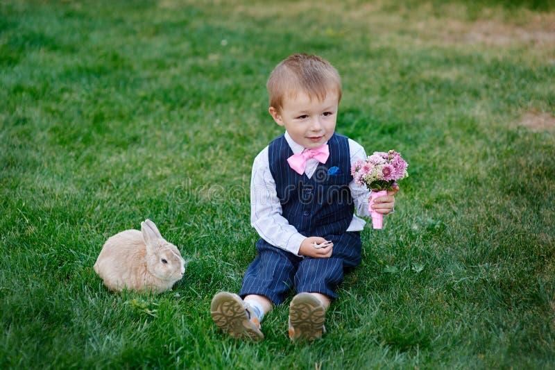 Chłopiec z bukietem kwiaty i królika obsiadanie na trawie fotografia royalty free