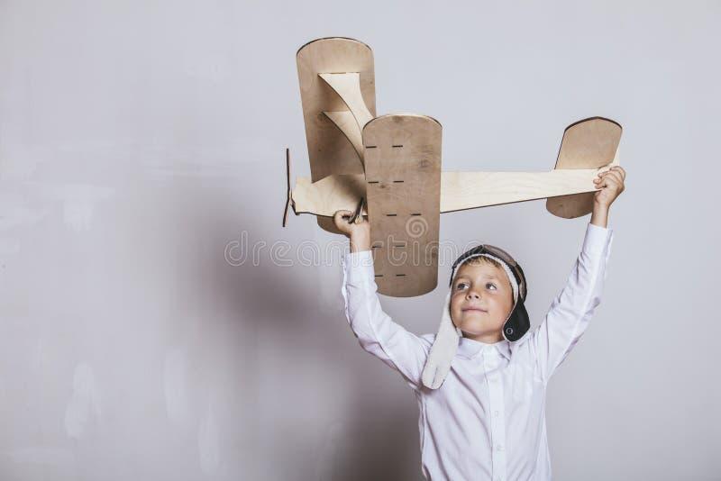 Chłopiec z drewnianym samolotu modelem i nakrętką z nakrętka projektami obraz stock