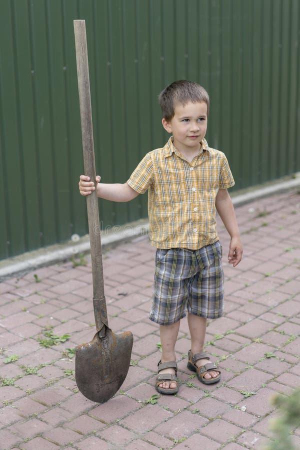 Chłopiec z dużą łopatą mała szczęśliwa chłopiec pracuje z łopatą w ogródzie chłopiec 5 lat utrzymuje dużą łopatę obrazy royalty free