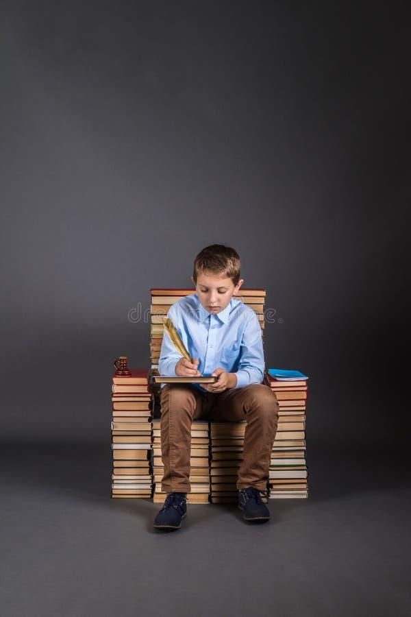 Chłopiec z dutki piórem siedzi na tronie książki obraz royalty free