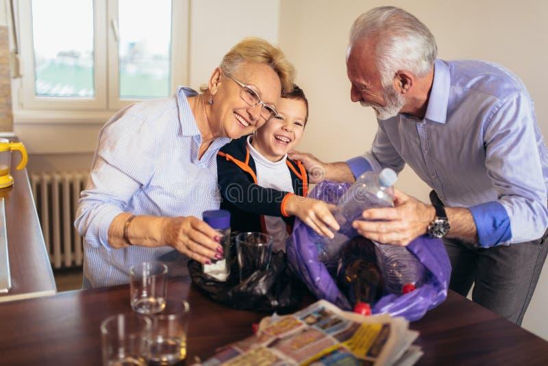 Chłopiec z dziadkami oddziela recyclable grat fotografia stock