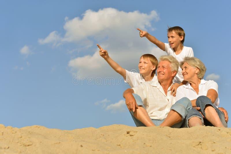 Chłopiec z dziadkami siedzi na piasku fotografia stock