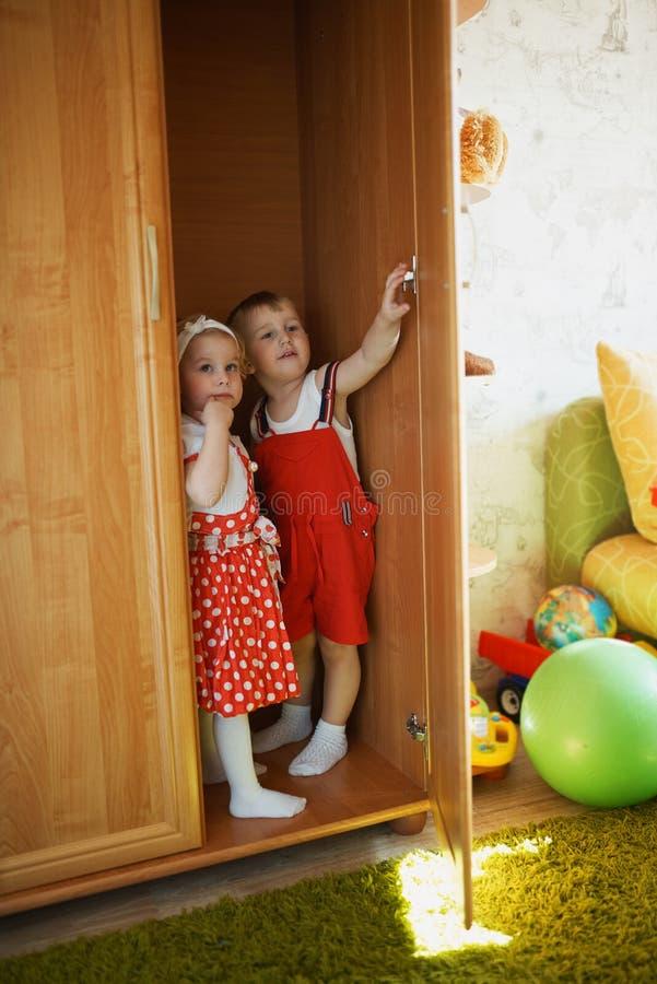 Chłopiec z dziewczyną bawić się kryjówkę aport - i - zdjęcie royalty free