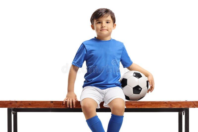 Chłopiec z futbolowym obsiadaniem na ławce obrazy royalty free