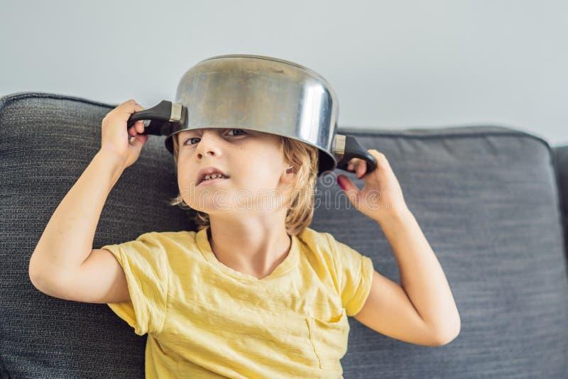 Chłopiec z garnkiem na jego głowie Dzieciństwo, kucharz fotografia stock