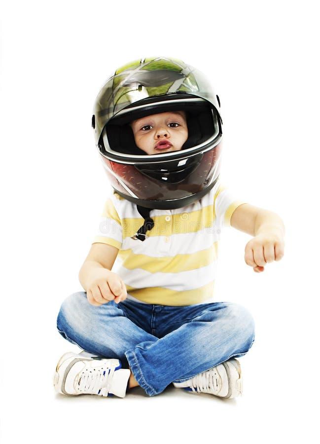 Chłopiec z hełmem, udaje jechać motocykl zdjęcie stock