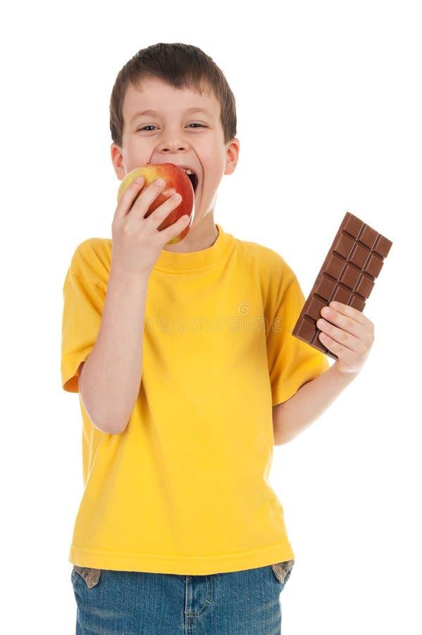 Chłopiec z jabłkiem i czekoladą obraz stock